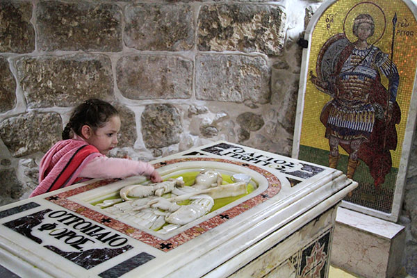 A young girl venerates the tomb of Saint George in Palestine