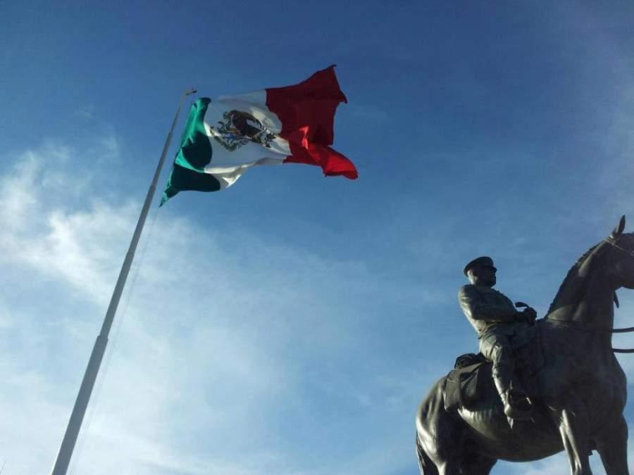 Bandera mexicana al lado del Monumento al General Álvaro Obregón
