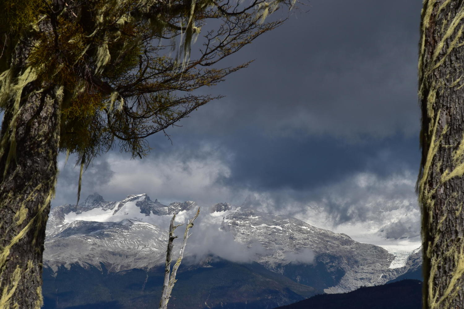 Moody clouds linger over a snow-capped peak along the Carretera