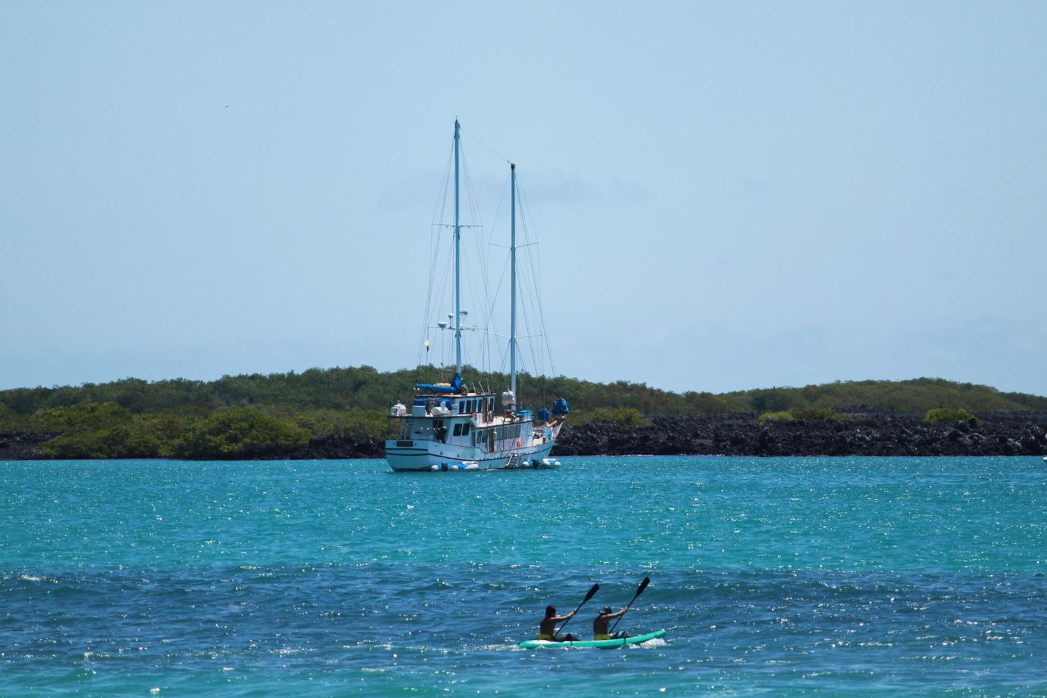 Paddling past the yacht Cachalote, Galapagos