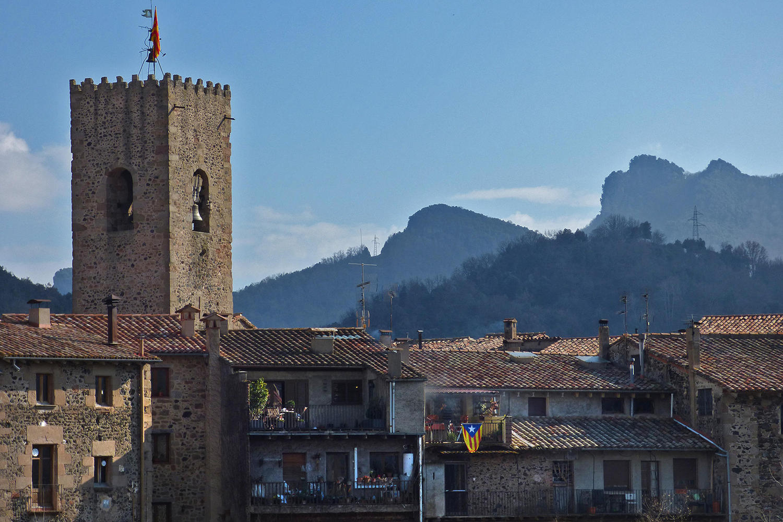 The castle of Santa Pau against the volcanic hills of Garrotxa