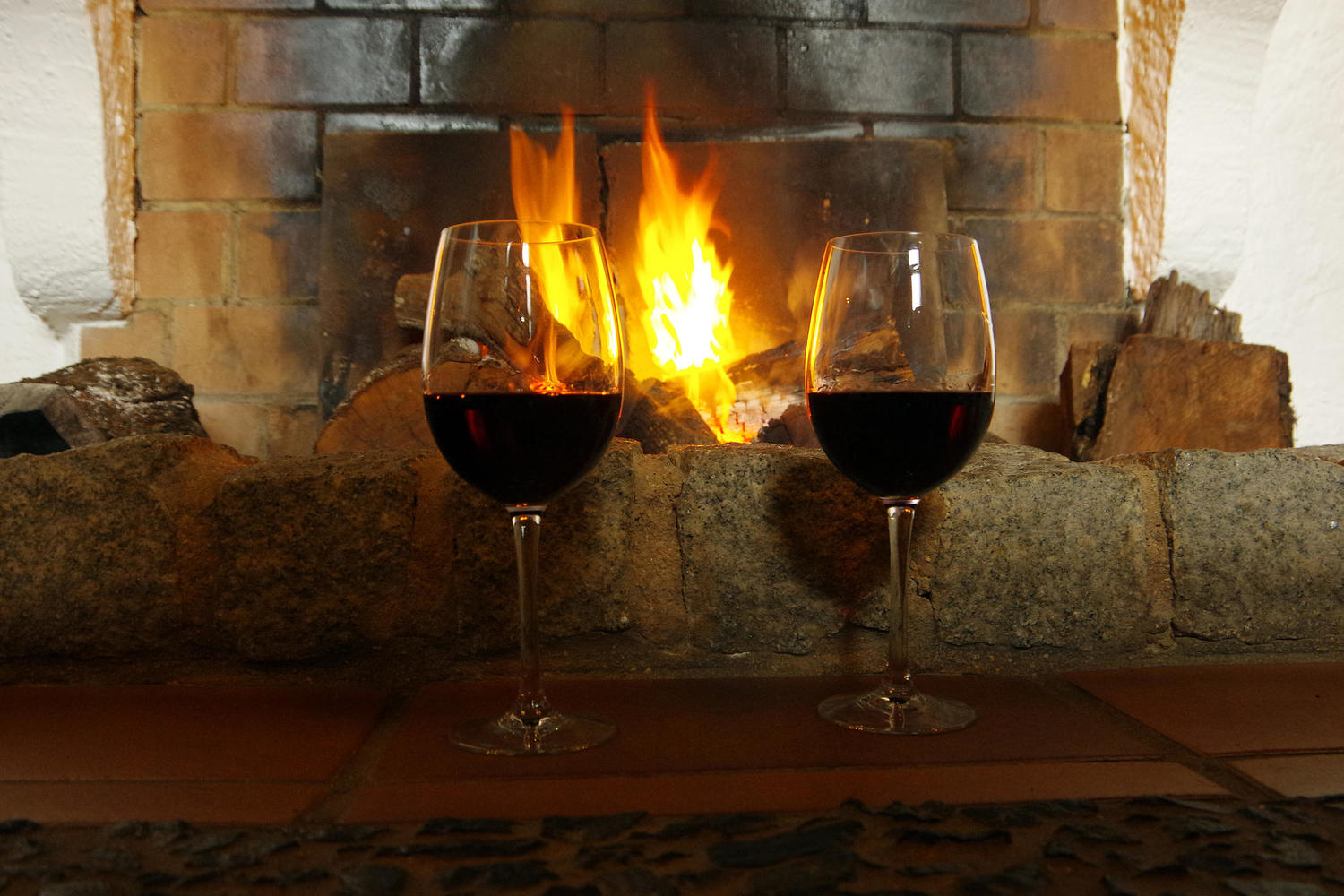 Glass of red wine warming in front of the fire in Linares