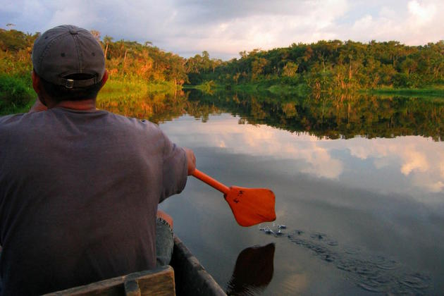 Ecuador amazon napo wildlife centre man paddling across black water lagoon red oar flip