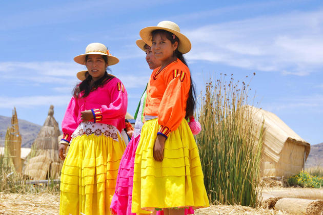 Peru lake titicaca unidentified women in traditional dresses welcome tourists in uros island