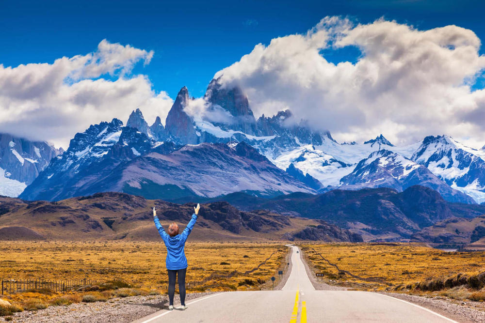 Argentina patagonia woman delighted natural beauty raised her hands. the highway leads to the snow capped peaks of mount fitzroy20180829 76980 a6ndlt