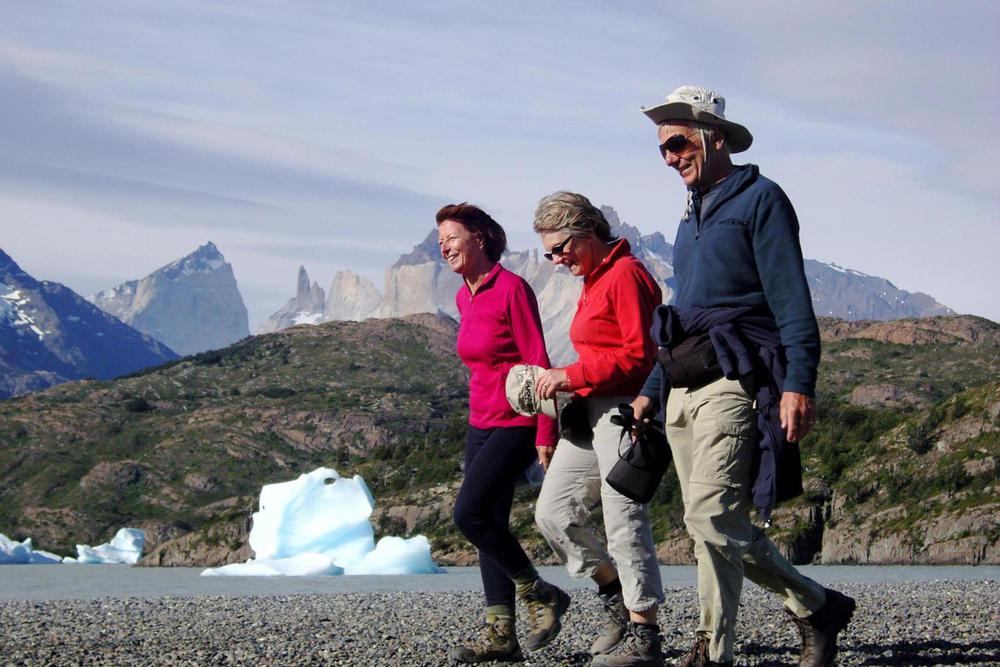 Chile patagonia torres del paine three walking along iceberg beach lago grey20180829 76980 17clj8p