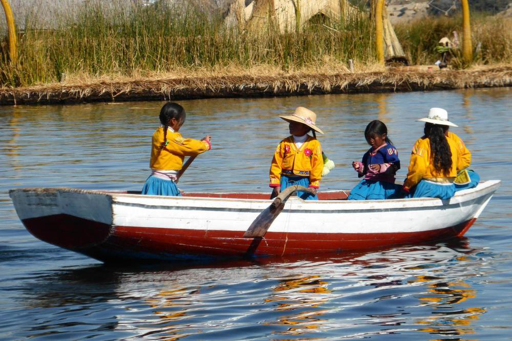 Peru lake titicaca young children dressed in yellow rowing boat20180829 76980 11wvqg6