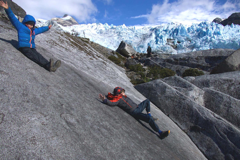 Boys sliding a glacier in Patagonia