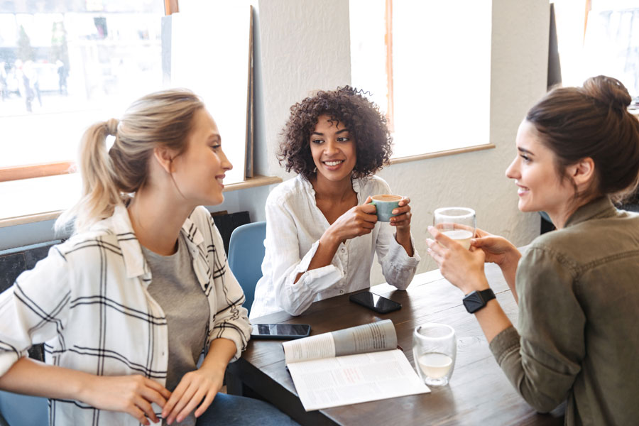 Three businesswomen sitting in cafe, drinking coffee and networking with each other