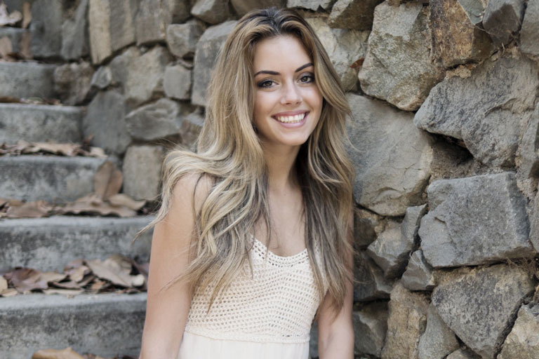 Young woman in sleeveless dress leaning against a stone wall and smiling