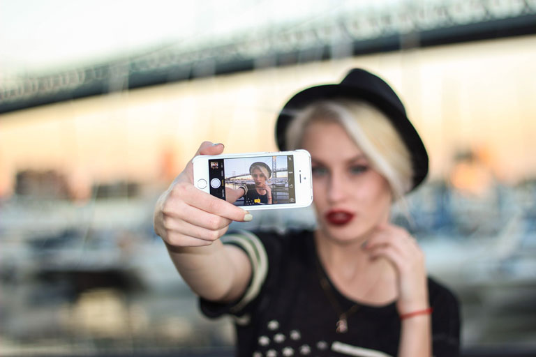 Young trendy woman with short hair, wearing a Fedora, taking a selfie