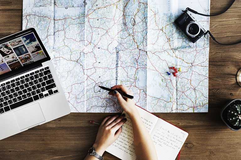 Woman planning trip using map, laptop, and notebook