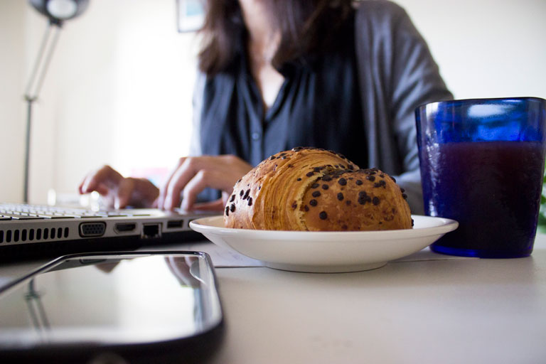 Woman typing on laptop with raisin toast and small glass of juice next to her