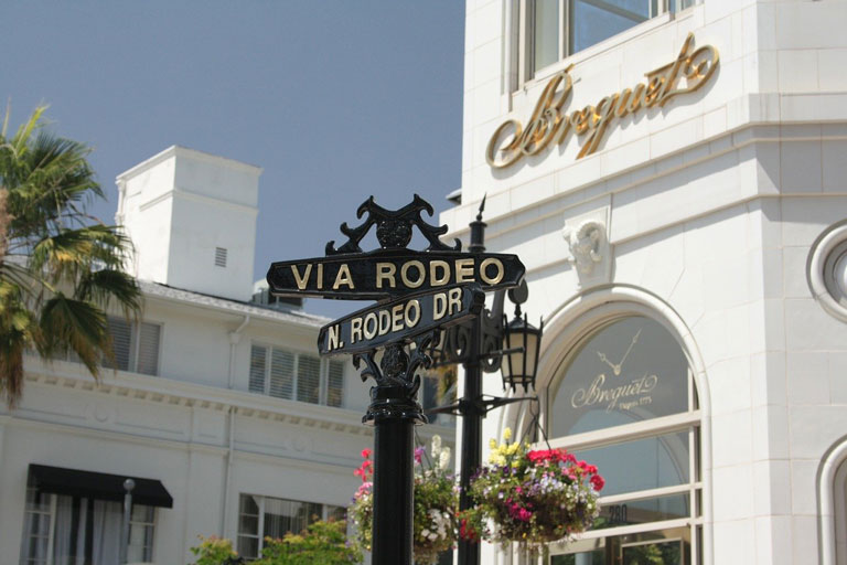 Rodeo Drive street sign with storefront in the background