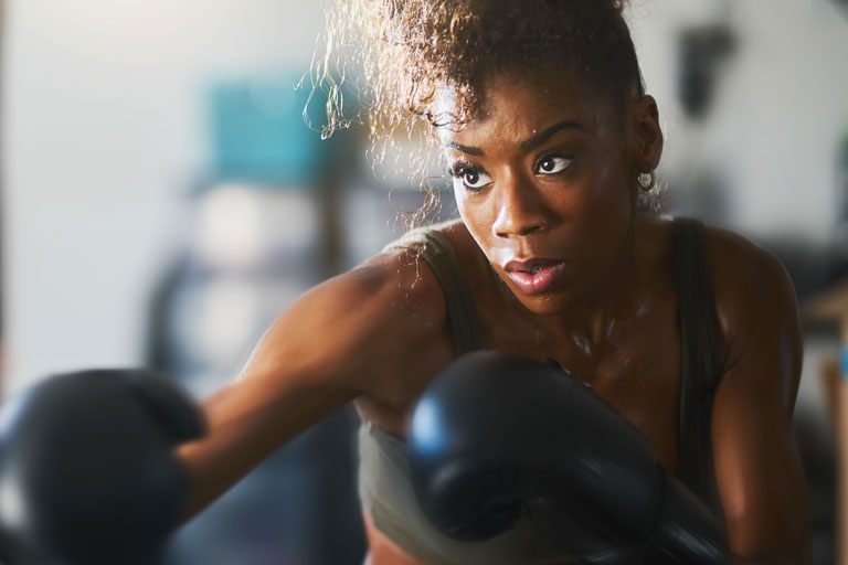 Young black woman wearing boxing gloves in sparring position