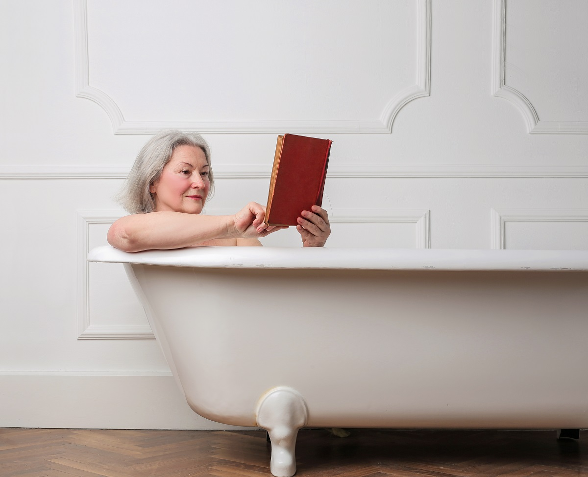 Elderly woman reading book in bath
