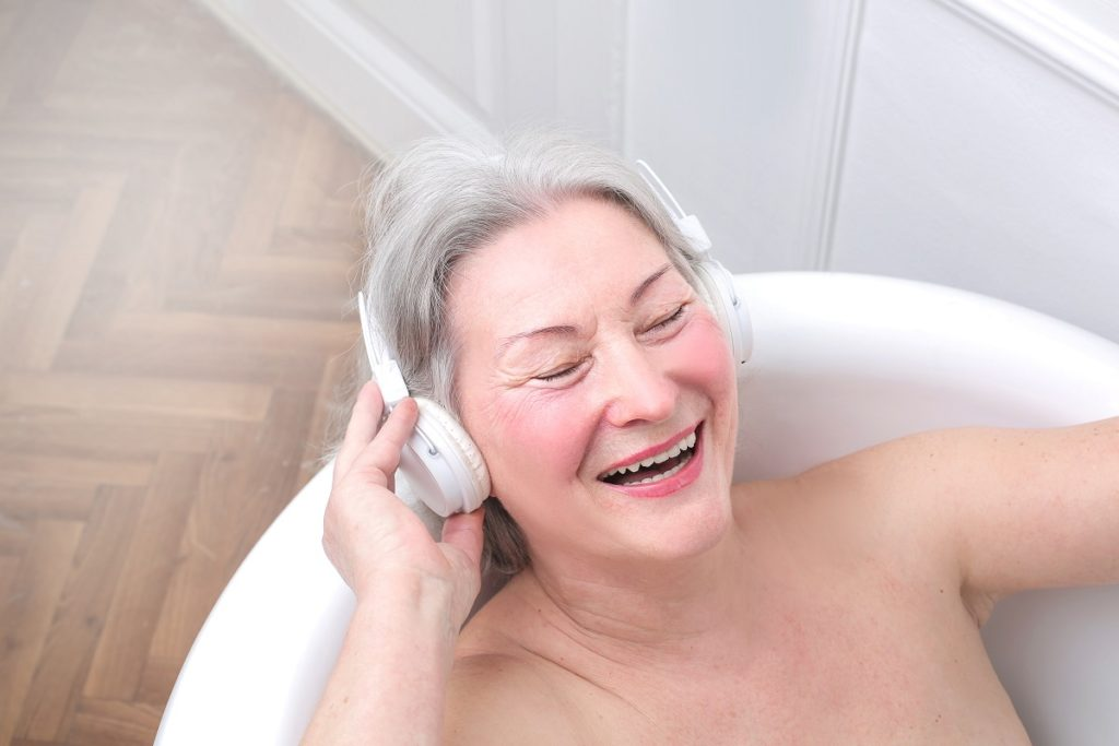 Elderly woman in bath with headphones on