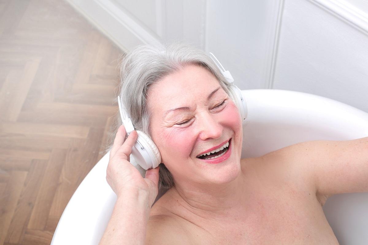 Elderly woman in bath with headphones on