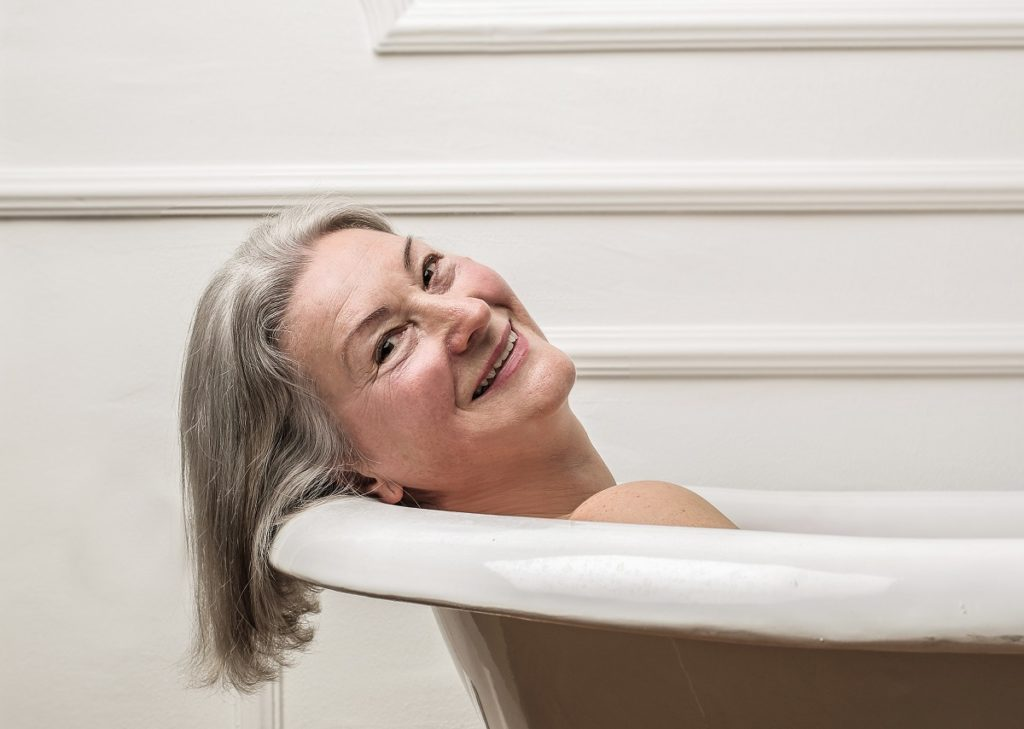 Elderly woman smiling in bathtub