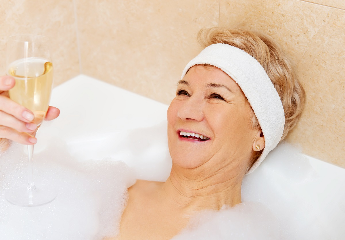 Senior woman drinking glass of wine in bubble bath