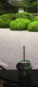 Image of sticks of incense burning in a Japanese garden