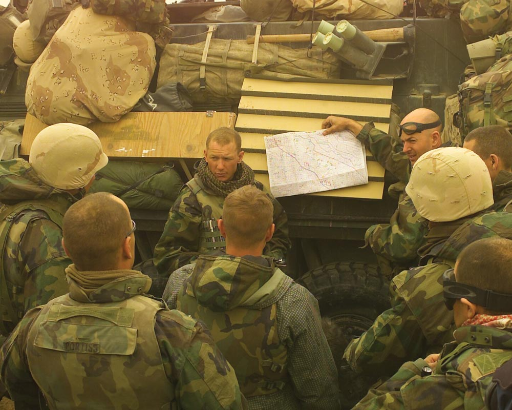 d3de9ea002677 Marine Corps Maj. Seth W.B. Folsom (center) briefs Delta Company staff on  Highway 1 in Iraq