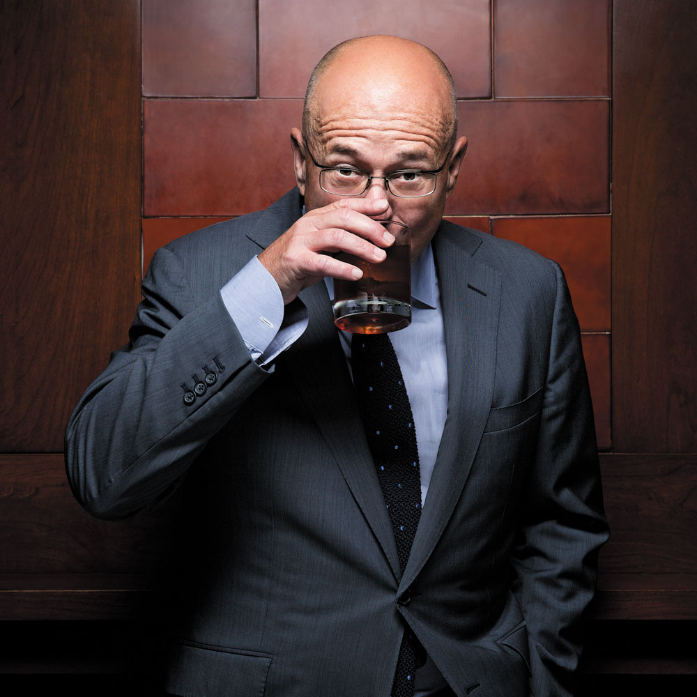 David Granger sipping a drink while wearing coat and tie