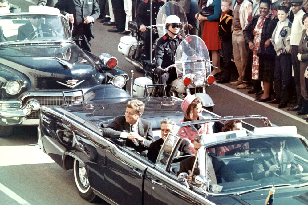 President John F. Kennedy riding in his limousine before being assassinated