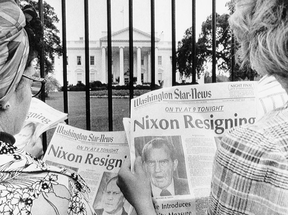 Two people outside the White House fence holding newspapers with the headline 'Nixon Resigning'