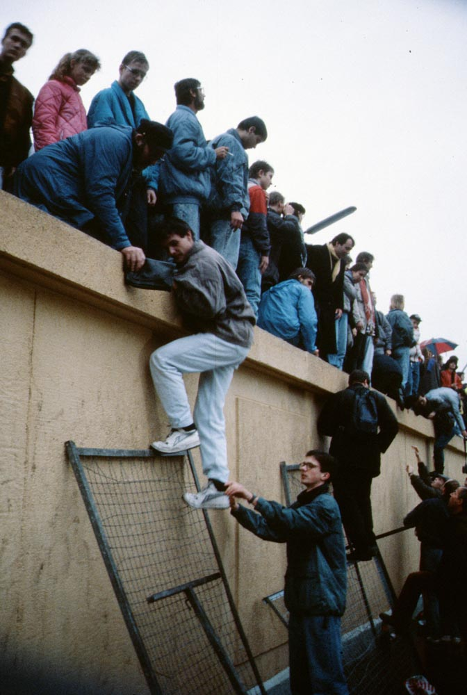 People climbing the Berlin Wall