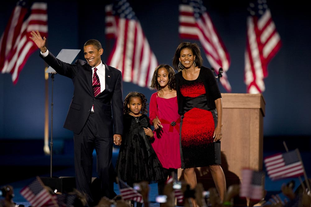 Barack Obama waves, accompanied by his family
