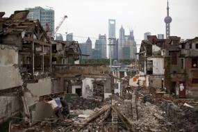 Migrant labourers work at a demolished residential site in downtown Shanghai