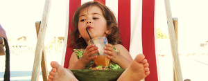 child sipping a drink in a beach chair