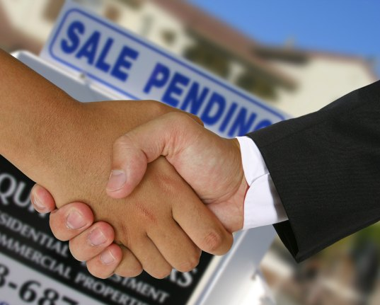 People shaking hands in a real estate transaction