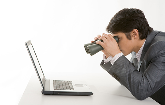 man looking at laptop with binoculars