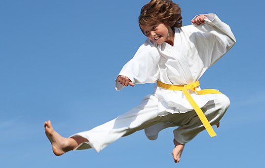 healthy fit kid doing karate leap or kick