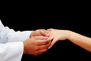 groom putting ring on bride's hand