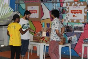 Bruno, Izy e Zamp, participantes do Dreammuro, organizam estande na Feira de Projetos.