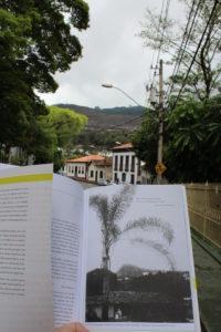 A imagem mostra o horizonte de Itabira e, em primeiro plano, uma foto antiga com o mesmo horizonte. A diferença entre o agora e o passado é que o morro presente na foto antiga já não existe mais por causa da exploração de minério no local.