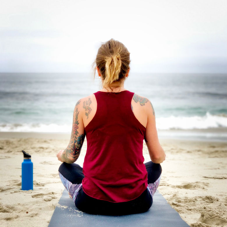 woman sitting on yoga mat on beach facing ocean, San Diego, CA