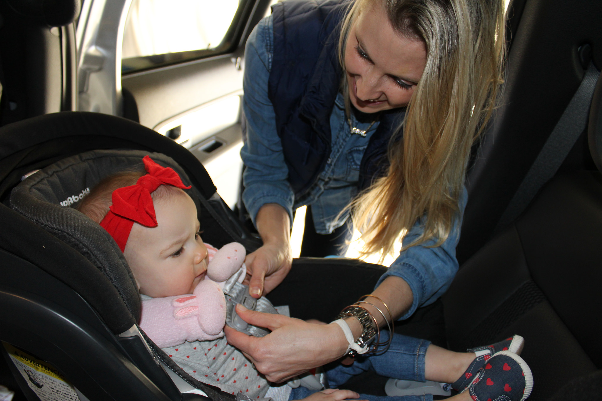 happy mom putting baby into car seat