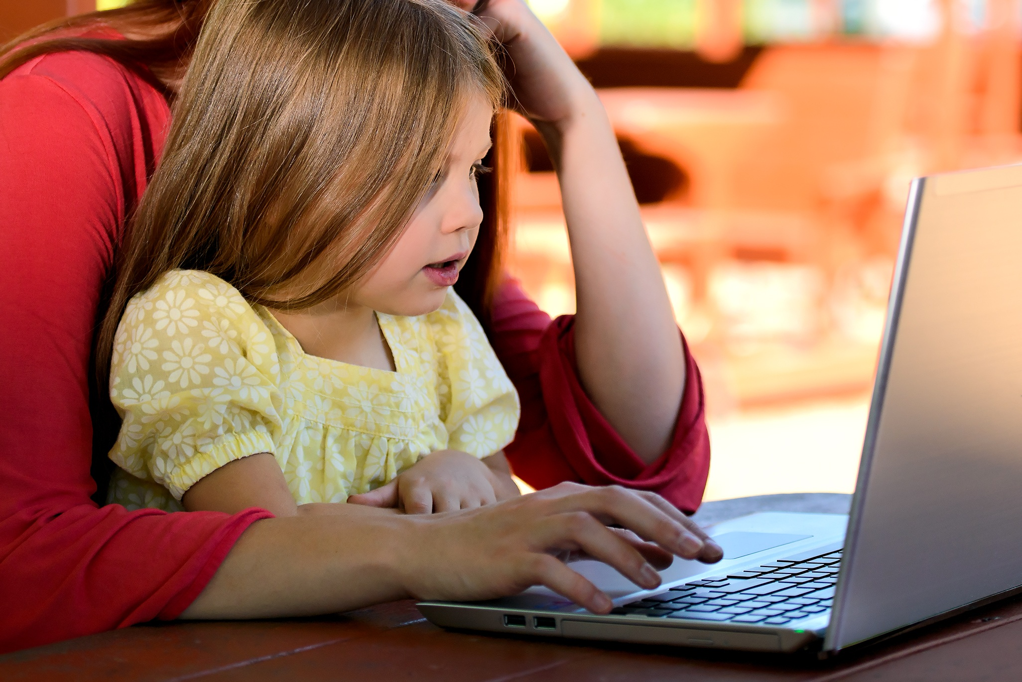Girl and mother in front of laptop