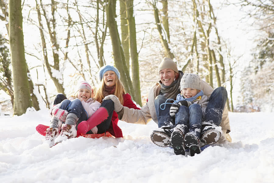A happy family sledding down hill in snow