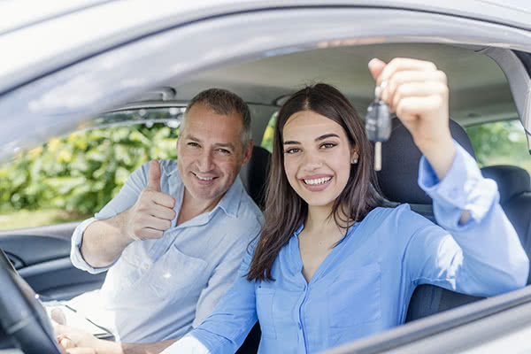 Teen girl driving with father in passenger seat