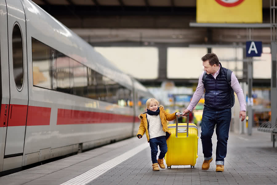 A father and young son pull a suitcase at a train station
