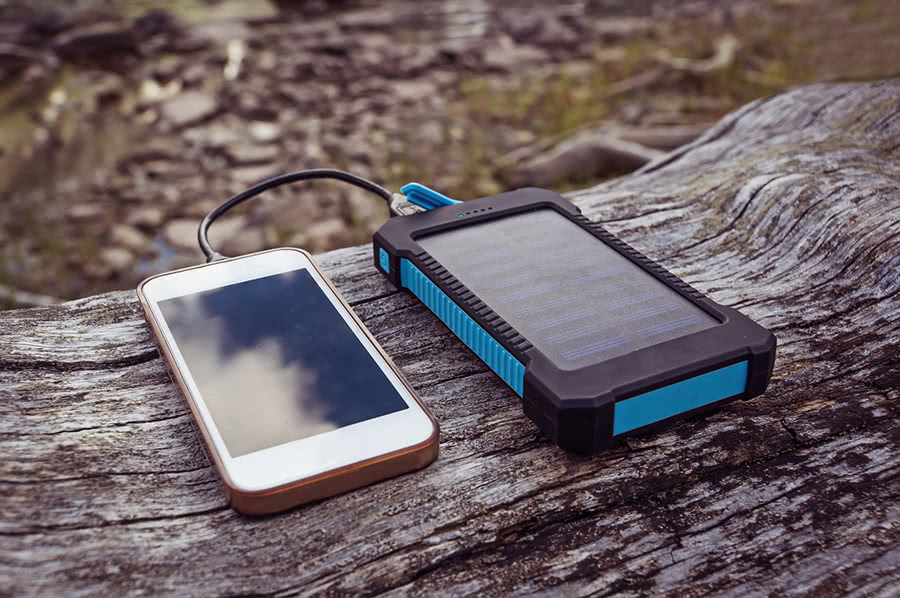A portable solar charging device refueles a smartphone sitting on a log