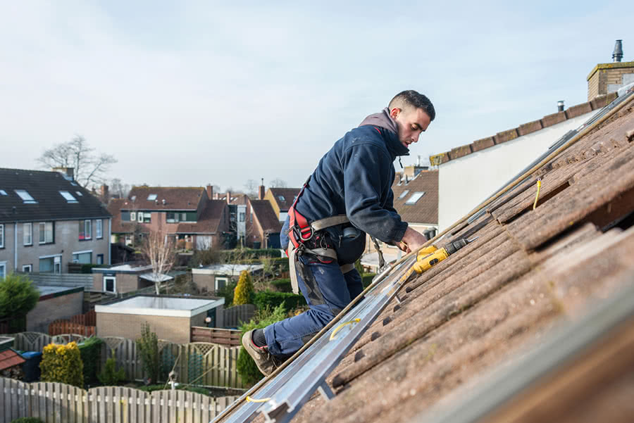 A man installs solar panels on the roof of a residential building