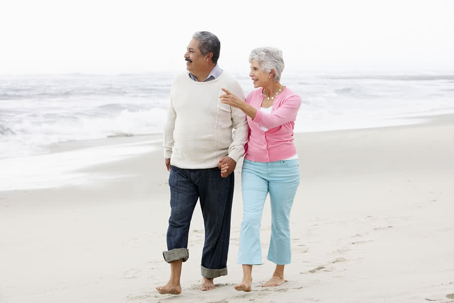 A retired couple walks barefoot along the shore