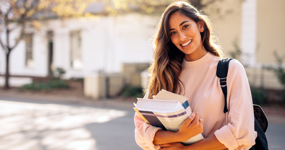 A graduate student who is considering egg donation carries her books across a university campus.