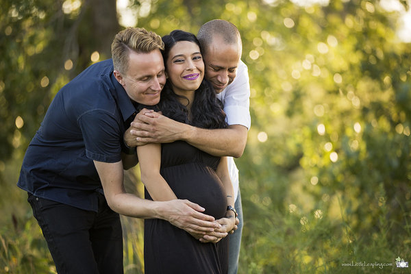 Pregnant woman smiling and cradling belly while being embraced by two happy men.